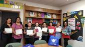 Seven adults hold their EFNEP graduation certificates along with the nutrition educator.