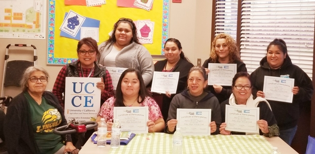 Elia Escalante (holding the UCCE board) with her participants who graduated from CFHL, UC program received certificate of completion.
