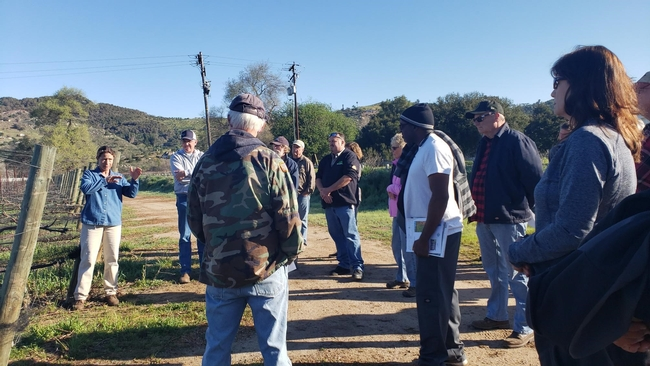 Ester field day participants are gathered outside for a demonstration.