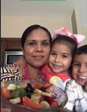 A family that attended class is showcasing their prepared Summer Fruit Salad recipe.