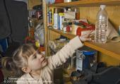 A child reaching for a pesticide stored in a common drinking container. (Credit: ML Poe)
