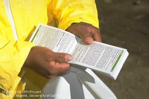 Reading pesticide label instructions. (Credit: Jack Kelly Clark) for Pests in the Urban Landscape Blog