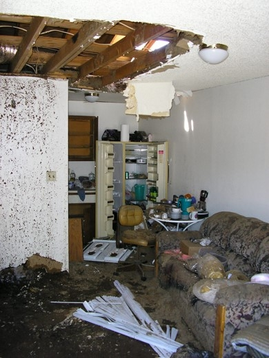 Living space with damage to ceiling and debris resulting from explosion.