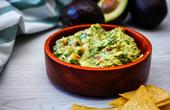 Bowl of guacamole with tortilla chips on the side.