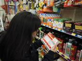 Person reads a pesticide label in the retail aisle.