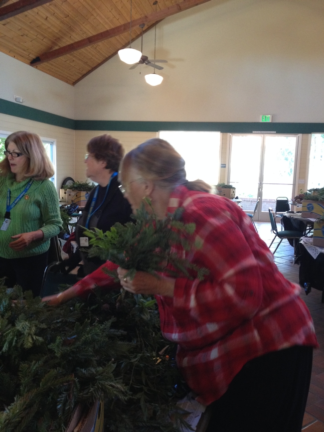 Master Gardener Sherry is creating a wreath.