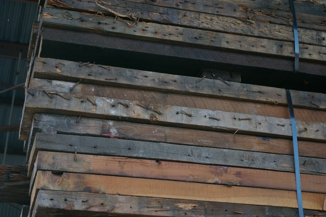 Lumber prior to processing - note the nails that all have to be removed by hand