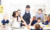 El médico residente Andrew Nuibe ayuda a niños de kínder a sexto grado del club de tareas de después de la escuela a preparar sus propios bocadillos saludables y a prevenir obesidad infantil
