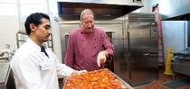 El chef Bob Walden (derecha) y Arnulfo Herrera, cocinero, muestran los tomates asados en la Universidad de California en Davis. (Foto por: Gregory Urquiaga/UC Davis) for Blog de Alimentos Blog