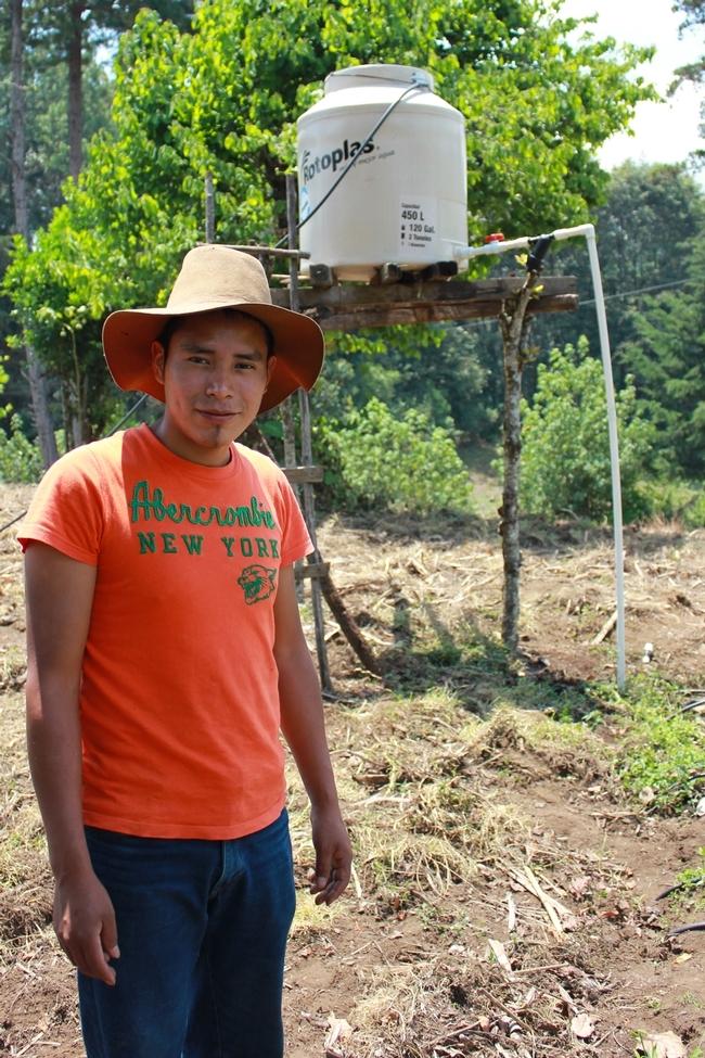 Miguel Isaías Sánchez usando el riego por goteo y una torre de agua e información ofrecida en entrenamientos de MásRiego. (Fotografía de Beth Mitcham).