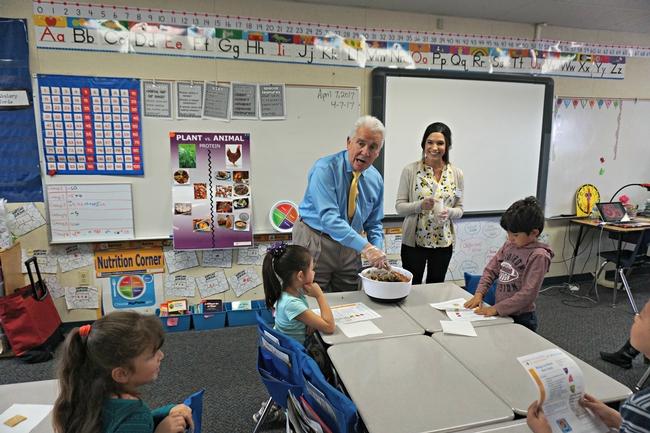El congresista de EUA Jim Costa mezcla la ensalada para los estudiantes de la primaria La Vina en el condado de Madera County. La educadora de nutrición de UCCE, Angélica Pérez junto al congresista.