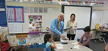 El congresista de EUA Jim Costa mezcla la ensalada para los estudiantes de la primaria La Vina en el condado de Madera County. La educadora de nutrición de UCCE, Angélica Pérez junto al congresista. for Blog de Alimentos Blog