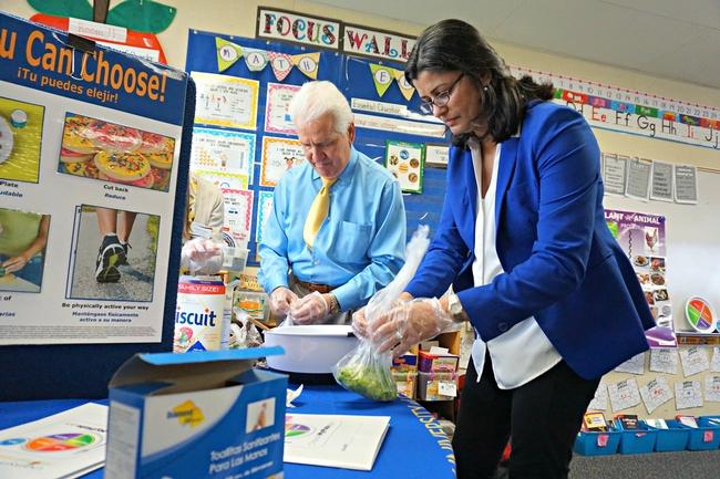 Pies de grabado El congresista de EUA Jim Costa y Mandeep Virk Baker, asesora de ciencias de la familia y del consumidor de UCCE, para Fresno y Madera, preparan los ingredientes para la ensalada.