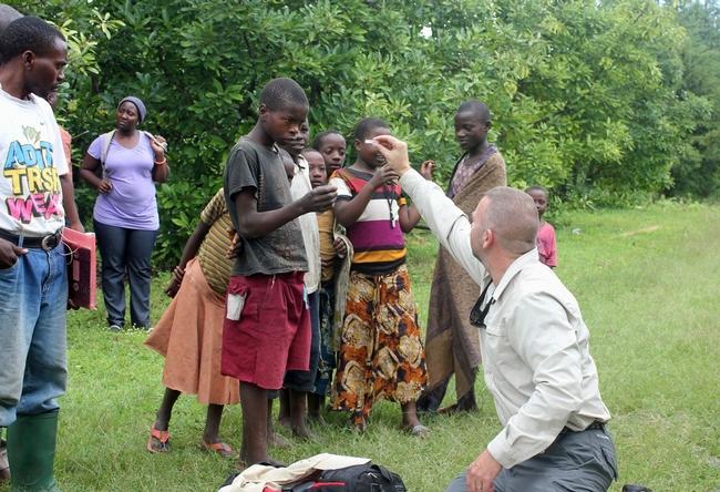 Mark Hoddle comparte algunos insectos con niños que se muestran interesados en una huerta de aguacates en el distrito Rungwe en Tanzania. (Fotografía: Mary Lu Arpaia)