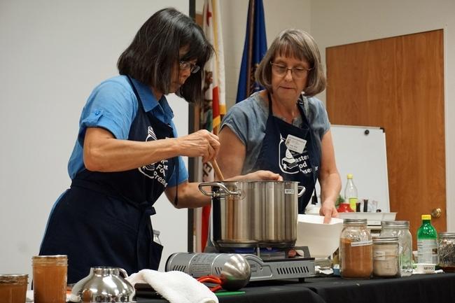 La coordinadora del programa de Conservadores Maestros de Alimentos de UC en el condado de Orange, Cinda Webb, derecha y Mabel Alazard, Conservadora Maestras de Alimentos, preparan mermelada de persimo.