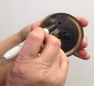 Marcar las tapaderas una vez que las ha usado, es una forma fácil de mantenerlas separadas de las nuevas. (Fotografía: Programa Maestro para Conservar Alimentos de UC)