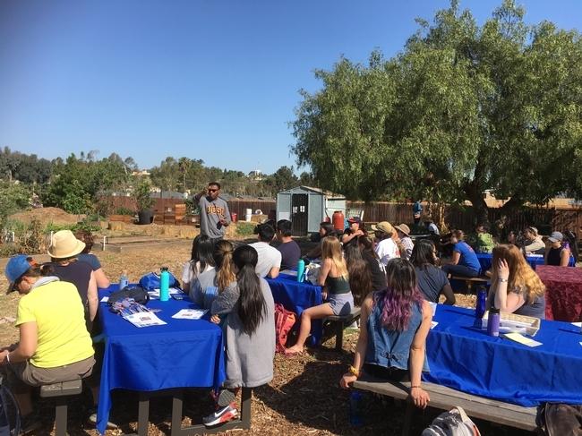 """Paul Watson, presidente y CEO del Centro de Investigación Acción Global, presenta los Ocean View Growing Gardens a los miembros de la GFI. """"No solo aplicamos los más recientes estudios sobre medioambiente a través de nuestra cooperación con UCSD, sino también trabajamos muy de cerca con líderes comunitarios y aprendemos cómo utilizar los alimentos como una herramienta de organización en este vecindario"""", señaló Watson."""