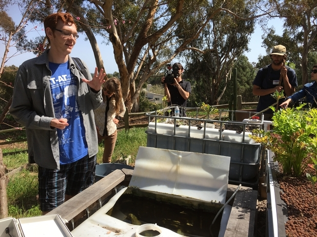 Un estudiante de UCSA habla sobre un sistema de circuito cerrado de acuaponía creado en el Huerto de Roger. Varios estudiantes de UCSD, así como miembros de la GFI conducen proyectos de investigación en el huerto con el objetivo de replicarlos y extenderse a huertos fuera de UCSD y en la comunidad.