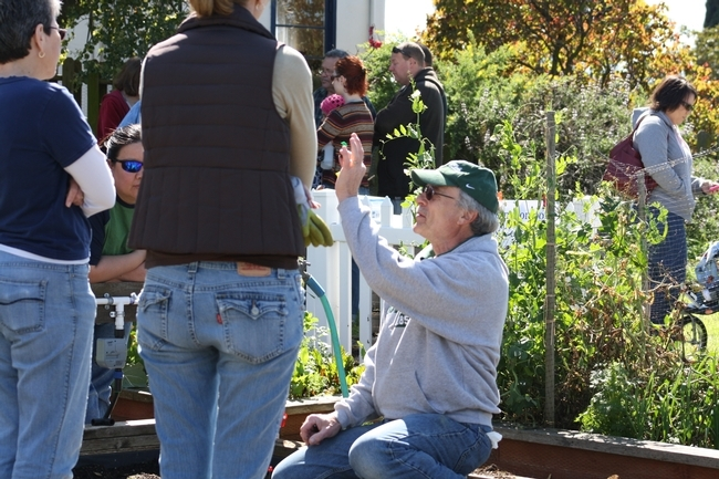 Mike G., voluntario del Programa Jardineros Maestros de UC, en el condado de Solano, muestra a los participantes partes del sistema de riego para huertos caseros.