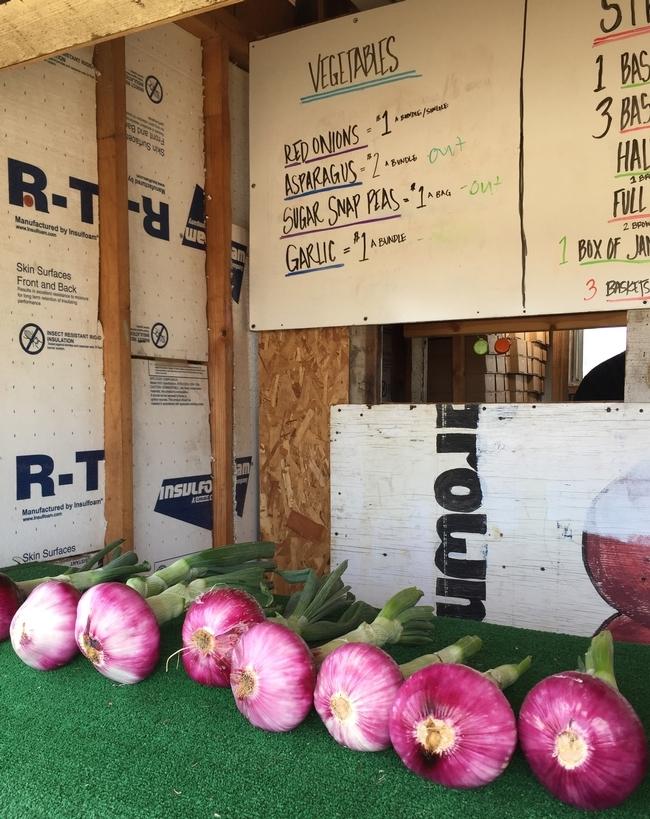 Algunos puestos de granjeros ofrecen verduras, como estas cebollas moradas, para complementar la venta de fresas.