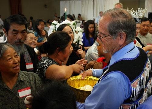 Miembros de la audiencia atan cordones a las muñecas de Molinar y le ofrecen huevos, galletas y otras muestras de apreciación tras haberle dado un nombre hmong.