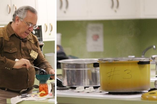 Prendergast vierte agua caliente con un cucharón en un frasco lleno de zanahorias, mientras que el agua se caliente en las ollas de presión para envasar.
