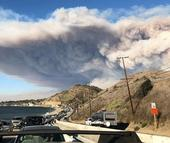 Traffic is backed up on Pacific Coast Highway as residents evacuate Malibu as a smoke plume from the Woolsey Fire rises in the background. (Photo: Wikimedia Commons)
