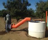 Groundwater is drawn by a pump to irrigate almonds in Fresno County.