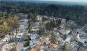 Drone footage of the Camp Fire aftermath shows homes destroyed while green trees are unscathed.