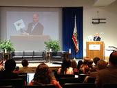 Gov. Brown holds a map showing temperature increases at climate change conference.
