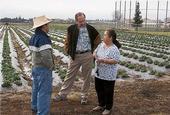 Michael Yang, left, and Richard Molinar, center, talk to a Southeast Asian farmer.