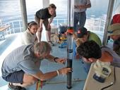 Researchers and students examine a sediment core sample from the bottom of Lake Atitlan.