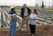 Michael Yang, left, and Richard Molinar advise a small-scale farmer.