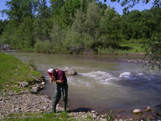 Larry Forero checks water transparency of Cow Creek. Photo by Lisa Thompson.