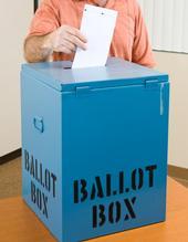 Person putting a ballot into a ballot box.
