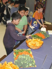 Children at a UCCE event enjoying fresh fruit and vegetables.