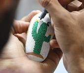 Entomologist Joel Hernandez adds the finishing touches on a rock painted by his wife, Melissa Cruz, the outreach coordinator for the UC Davis Arboretum and Public Garden. (Photo by Kathy Keatley Garvey)
