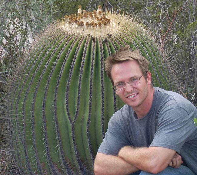 Alex Van Dam, photographed next to a giant cactus.