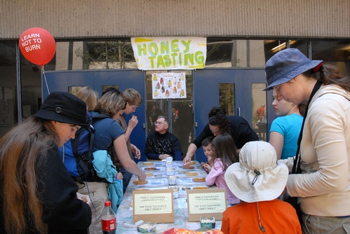 COOPERATIVE EXTENSION APICULTURIST Eric Mussen (center) answers questions about honey at the annual honey tasting table at Briggs Hall, UC Davis. (Photo by Kathy Keatley Garvey)