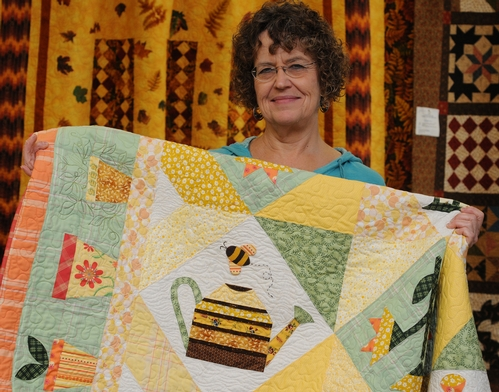 A HONEY BEE decorates a quilt at the 134th annual Dixon May Fair. Here Interior Living Showcase superintendent Debee Lamont gets ready to hang the quilt. It's the work of Shirley Geertson of Vacaville. (Photo by Kathy Keatley Garvey)
