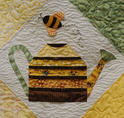 CLOSE-UP of a honey bee and a plant watering can on a quilt at the Dixon May Fair. This quilt is the work of Shirley Geertson of Vacaville. (Photo by Kathy Keatley Garvey)