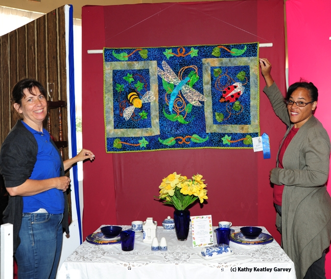 Gloria Gonzalez (left) of Vallejo, superintendent of McCormack Hall, Solano County Fair, and assistant Iris Mayhew of Vallejo hang a quilt by LaQuita Tummings of Vallejo. (Photo by Kathy Keatley Garvey)