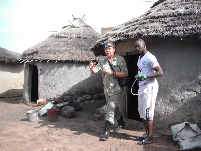 UC Davis medical entomologist Anthony Cornel (left) emerges from a hut in Mali.