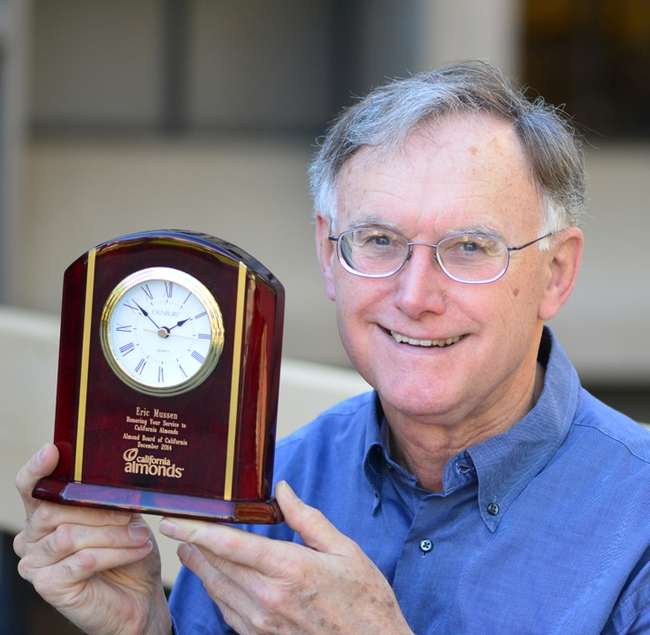 Extension apiculturist (emeritus) Eric Mussen with his engraved clock from the Almond Board of California. (Photo by Kathy Keatley Garvey)