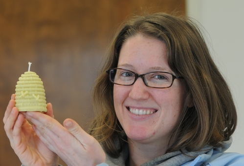 BEEKEEPER Elizabeth Frost shows a miniature beehive candle she made from beeswax and a little paraffin. (Photo by Kathy Keatley Garvey)