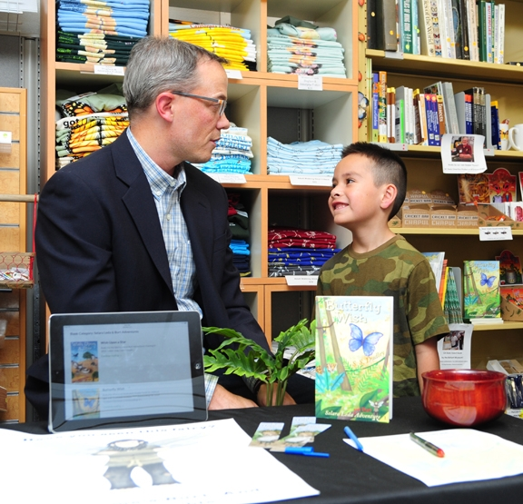 Joel Fuerte, 6, of Woodland, eagerly listens to children's author S. S. Dudley, a retired UC Davis scientist. (Photo by Kathy Keatley Garvey)