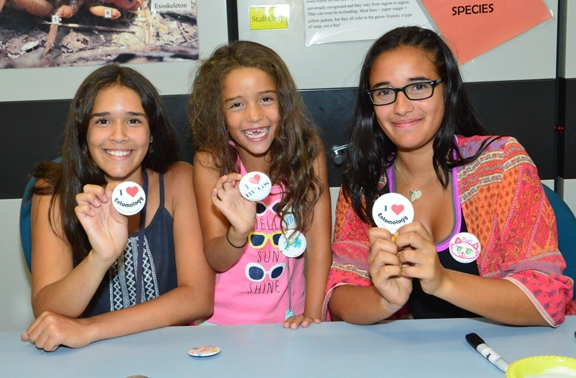 The Nansen sisters (from left) Emma, 12, Molly, 6, and Miriam, 15, of Davis display entomology buttons. They helped visitors create buttons. Their mother, Maria, is a volunteer at the Bohart, and their father, Christian, is a UC Davis entomologist. (Photo by Kathy Keatley Garvey)