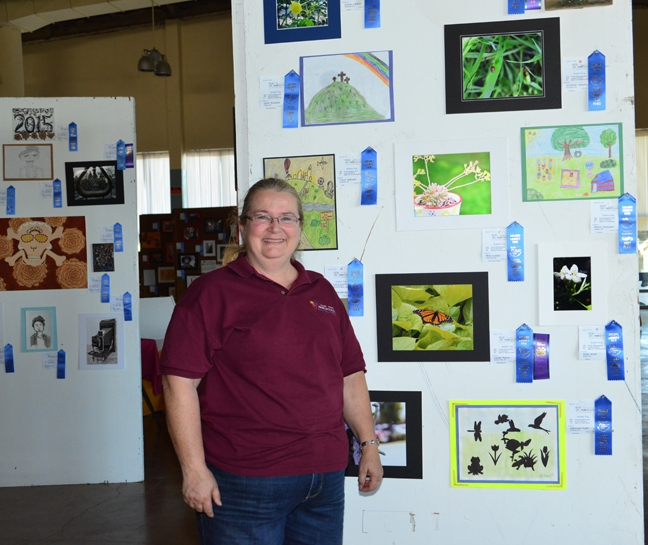 McCormack Hall assistant superintendent Sharon Payne of Vallejo, a past president of the Solano County 4-H Leaders' Council, stands next to youth photography featuring insects. (Photo by Kathy Keatley Garvey)