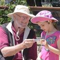 Native pollinator specialist Robbin Thorp, distinguished emeritus professor of entomology, shows a bee to haven visitor Lalibella Eaves, 6, of Quebec City, Canada. Her mother,  Valerie Fournier, received her doctorate in entomology from UC Davis in 2003 and is now a professor at Laval University, Quebec City. (Photo by Kathy Keatley Garvey)