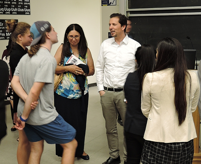 Dr. Emanual Maverakis (in white shirt), Department of Dermatology, UC Davis School of Medicine, answers questions after the symposium. (Photo by Kathy Keatley Garvey)